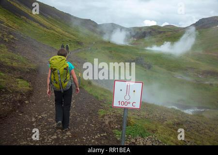 Escursionista passando hot springs nella valle di Reykjadalur. Hveragerdi, sud dell'Islanda.