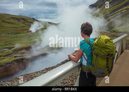 Escursionista accanto a sorgenti termali nella valle di Reykjadalur. Hveragerdi, sud dell'Islanda.