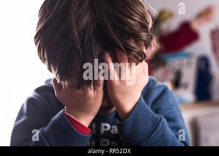 Little Boy copre gli occhi per la paura o imbarazzo in primo piano immagine Foto Stock