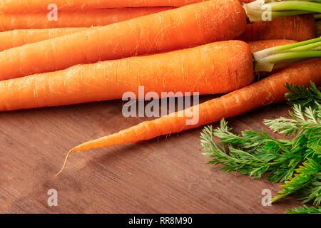Fresche materie organiche carote al buio su un rustico sfondo di legno con un posto per il testo Foto Stock