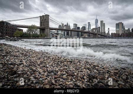 Una spiaggia di ciottoli sull'East River a Brooklyn guardando verso il ponte di Brooklyn e la parte inferiore di Manhattan, New York, Stati Uniti d'America Foto Stock