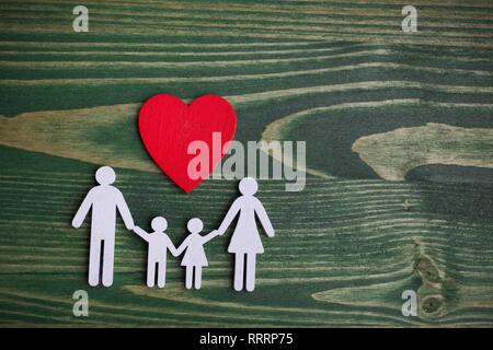 Family Health, assicurazione vita concetto. Catena di legno in forma di famiglia con cuore rosso. Vista superiore, laici piatta Foto Stock