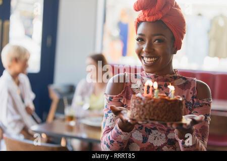 Ritratto sorridente, fiducioso giovane donna holding torta di compleanno con candele Foto Stock