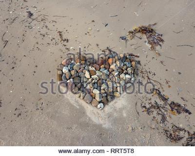 A forma di cuore di pietra con un po' di alghe sulla spiaggia sabbiosa Foto Stock