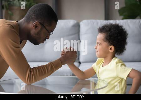 Africana di papà e figlio di capretto con divertenti visi arrabbiati armwrestling Foto Stock