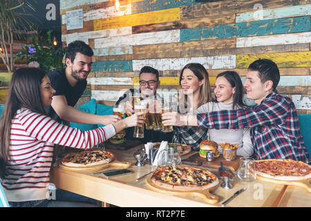 Felice giovani amici bevendo birra a parte nel pub alla moda Foto Stock