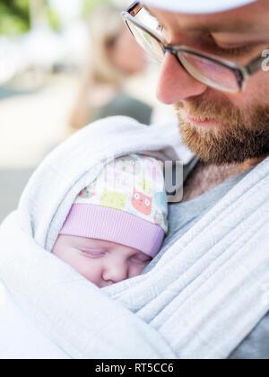 Padre portando la sua bimba sul suo petto in una imbracatura Foto Stock