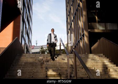 Imprenditore a piedi giù per le scale nella città Foto Stock