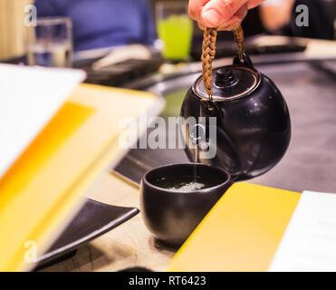 Bere caldo a base di erbe gustoso tè verde Matcha in terracotta nera cup, che serve da bollitore nel ristorante dello sfondo. Avendo sano medicinali naturali bever Foto Stock