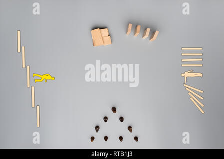 Vista superiore dei cubi di legno, pioli, scacchi pezzi di carta e di tagliare la gente di affari collocato su uno sfondo grigio in un'immagine concettuale della visione aziendale, strateg Foto Stock