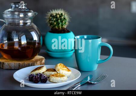 Una sana colazione a base di frittelle di ricotta con frutti di bosco e tè verde in un bicchiere tè pentola. La dieta dolce concetto.