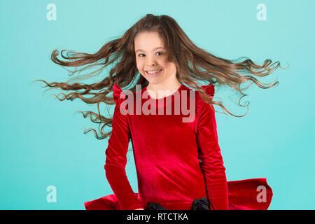 Piccola ragazza sorriso con battenti capelli su sfondo blu, moda. Bambino sorridente con lunghi brunette acconciatura in abito rosso. Salone di bellezza concetto. Cura dei capelli -, parrucchiere, barbiere. Incalzanti trend pastello Foto Stock