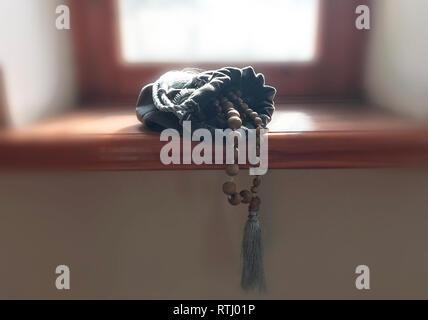 Legno di Tulasi rosario giacciono su una roccia fondo in erba verde. Japa mala. Mantra. 108 perline. Foto Stock