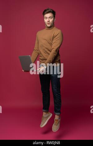 A piena lunghezza Ritratto di un allegro giovane uomo che indossa abiti casual isolate su sfondo rosa, tenendo il computer portatile, saltando. Foto Stock