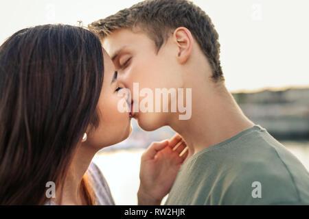 Romantico coppia giovane la condivisione di un bacio al di fuori nel pomeriggio Foto Stock