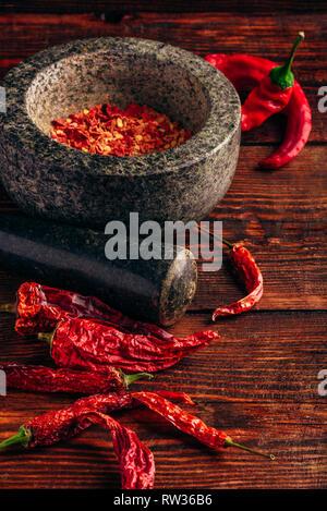 Essiccato e frantumato peperoncino rosso in mortaio di pietra Foto Stock