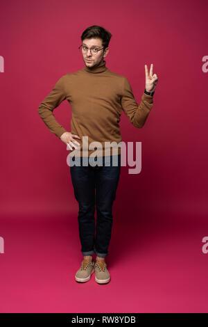 Uomo bello il conteggio con due dita isolato su sfondo blu. Foto Stock