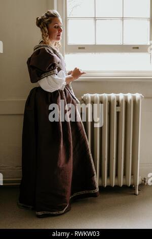 Ritratto di una giovane e bella donna in ornato abito storico- i suoi vestiti sono belle, sta in piedi da una porta nel profondo del pensiero e sembra triste.