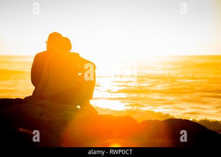 Tramonto sulla spiaggia di Hokitika con due giovani turisti ejoying il tramonto. Foto Stock