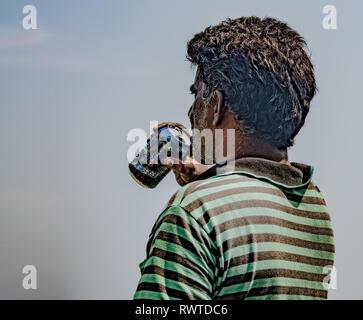Persone di mezza età pescatore del sud di origine asiatica, indossando striped tshirt è esaurito e si disseta bevendo birra/drink freddo nelle calde giornate di sole Foto Stock
