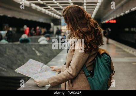 Giovane donna ricci testa rossa ragazza viaggiatori con zaino e mappa in metropolitana Foto Stock
