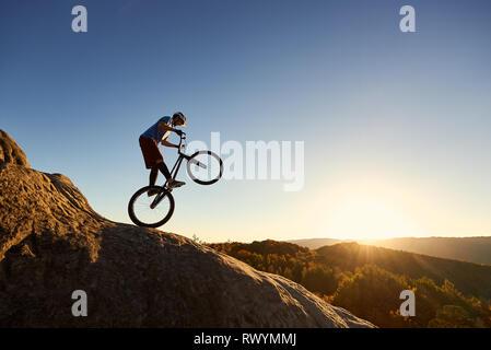 Silhouette di un ciclista professionista equitazione sulla ruota posteriore sul trial bike. Intrepido sportivo biker facendo acrobazie stunt sul bordo del grosso masso al tramonto. Concetto di sport estremo che uno stile di vita attivo Foto Stock