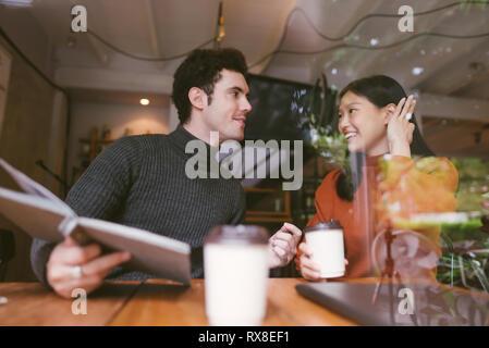 Felice ragazza asiatica e gli amici in chat parlando presso la caffetteria cafe nell università di mantenere il contatto visivo e ridere insieme,