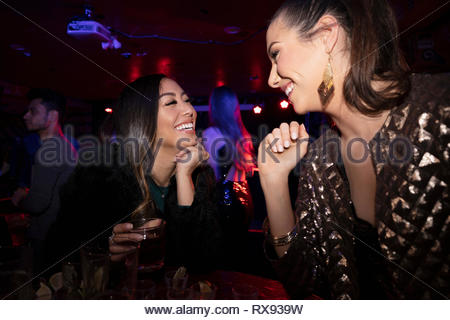 Felici donne gli amici a bere in discoteca Foto Stock