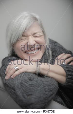 Ritratto giocoso, felice senior donna con i capelli grigi a ridere Foto Stock