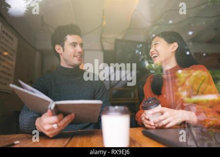 Felice ragazza asiatica e gli amici in chat parlando presso la caffetteria cafe in università a parlare e ridere insieme,