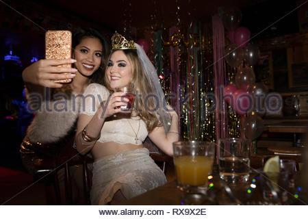 Addio al nubilato e amico tenendo selfie e bere un cocktail in discoteca Foto Stock