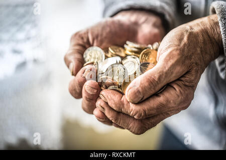 Titolare di pensione o di rendita uomo tenendo in mano delle monete in euro. Il tema delle pensioni basse Foto Stock