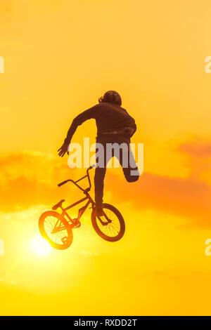 Giovane uomo facendo acrobazie in un salto sul suo bmx bike. Sunset silhouette retroilluminato Foto Stock