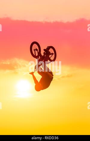 Silhouette di uomo di eseguire trucchi su bmx bike rosa contro il cielo al tramonto Foto Stock