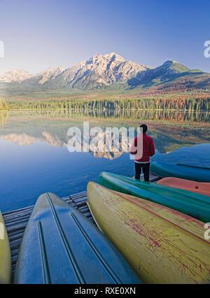 Lone medio di sesso maschile di età in piedi sul dock con canoe guardando a piramide in Montagna Lago Piramide, il Parco Nazionale di Jasper, Alberta, Canada