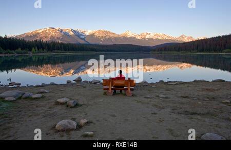 Metà maschio età seduta sul banco cercando Patricia Lake, il Parco Nazionale di Jasper, Alberta, Canada.