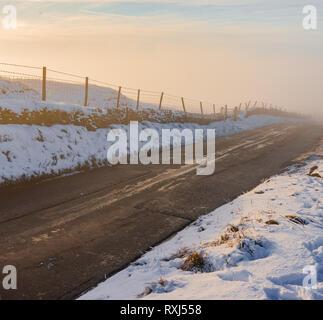 Un profondo nebbia sorge da una strada di campagna nel mezzo dell'inverno, 2019 Foto Stock