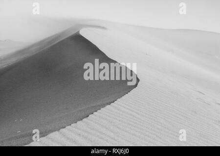 Dune ridge dettaglio, vicino. Increspature di sabbia e texture. La sabbia nel vento sullo sfondo. Deserto del Sahara. Il Marocco. Bianco e nero, monocromatiche. Foto Stock