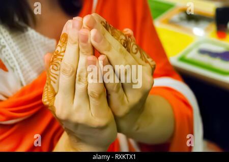 Una donna caucasica coppettazione le mani per mostrare il mehndi disegni su di lei le dita indice. Bokeh di fondo per la creatività. Shilparamam, Hyderabad, Telangana, India. Foto Stock