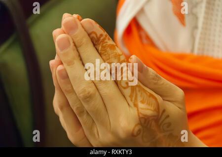 Una donna caucasica tourist coppettazione le mani per mostrare l'henna/mehndi designs sul suo indice della mano sinistra. Shilparamam, Hyderabad, Telangana, India. Foto Stock