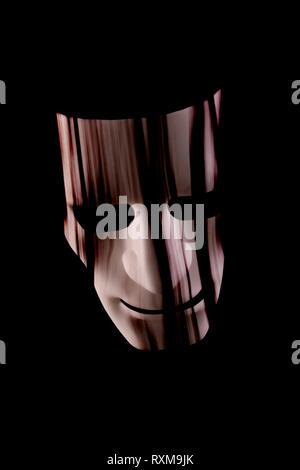 Scary maschera facciale con capelli appesa sopra la faccia. Nero scuro dello sfondo. Halloween o orrore o metropolitana il concetto di criminalità