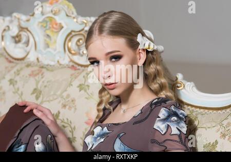 Bella ragazza bionda con capelli ricci seduto sul divano vintage. Closeup Ritratto di giovane donna in abito fiorito Foto Stock