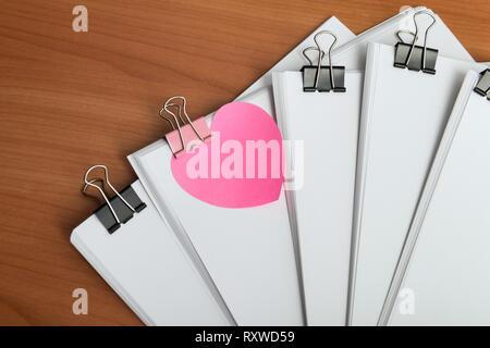Libro bianco documento con graffe di metallo legante sul tavolo di lavoro vista dall'alto. Forma di cuore promemoria sulla parte anteriore