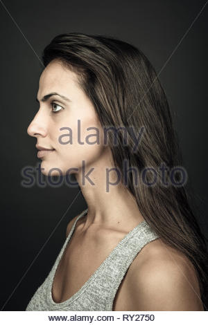 Ritratto di profilo considerato giovane e bella bruna donna con capelli lunghi Foto Stock