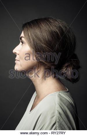 Ritratto di profilo riflessivo brunette bella donna che guarda lontano Foto Stock