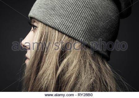 Ritratto di profilo premurosa donna bellissima con anello di naso in beanie Foto Stock