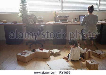 Il Toddler girl giocando con i regali di Natale sul pianale dietro la madre lavora al computer portatile Foto Stock