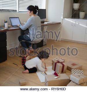 Il Toddler girl colorazione nei pressi di regali di Natale dietro la madre lavora al computer portatile Foto Stock