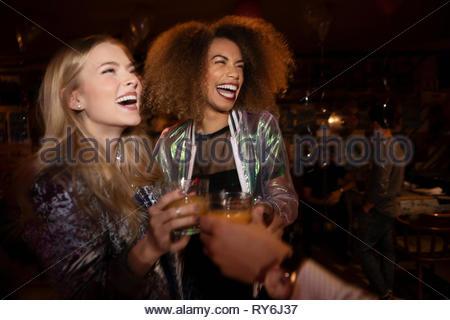 Ridendo di donne giovani amici di bere in discoteca Foto Stock