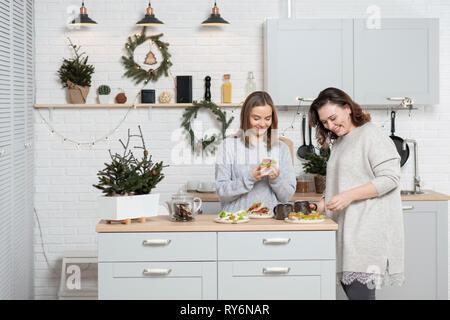 Donna sorridente amici parlare pur avendo il cibo e le bevande in cucina durante il periodo di Natale